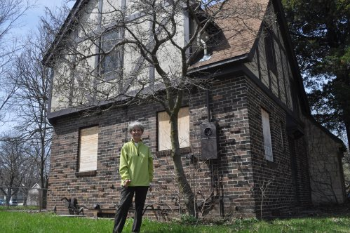 Sandy Paulsen stands in front of the Tudor-Revival style house where she raised 3 children in the '80s. The home was built in 1936. It goes to auction on Monday, but buyers would be required to move it out of the floodplain.